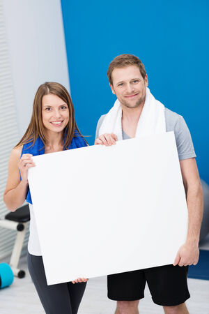 Healthy fit young couple standing in a gym in their sportswear holding a blank white sign with copyspace for your text or advertisement photo