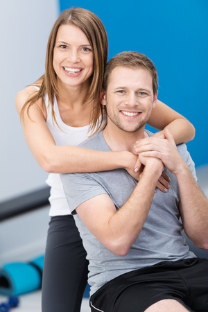 conscious: Affectionate health conscious young couple posing arm in arm at the gym looking at the camera with happy smiles Stock Photo