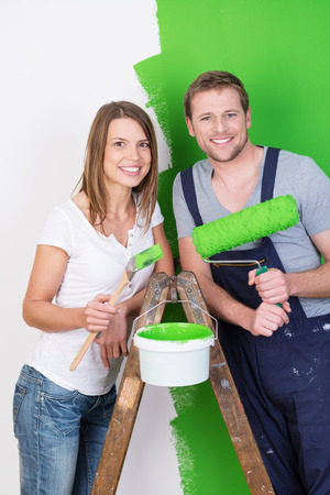 reforming: Husband and wife doing DIY renovations and redecorating their new home together painting it a bright green posing on a stepladder smiling at the camera Stock Photo