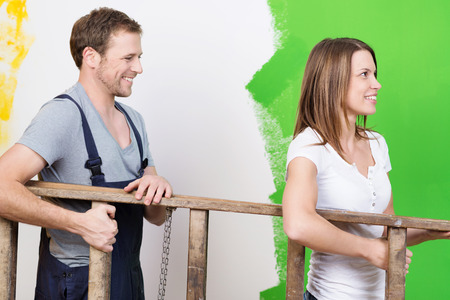 reforming: Happy young couple doing home redecorating carrying a wooden stepladder together as they paint the walls green Stock Photo