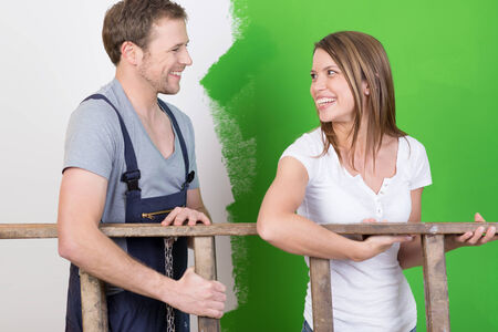 reforming: Happy young couple laughing together as they redecorate their new home and work as a team carrying a wooden stepladder
