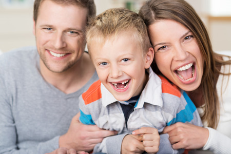 Laughing cute little boy with his front teeth missing posing with his friendly smiling young parents in a loving family portrait as they enjoy a bit of fun together photo
