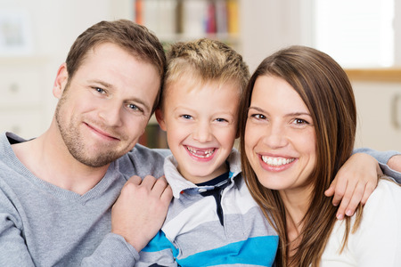 Beautiful happy young family posing together for a portrait with attractive young parents flanking a cute little boy with his front teeth missing