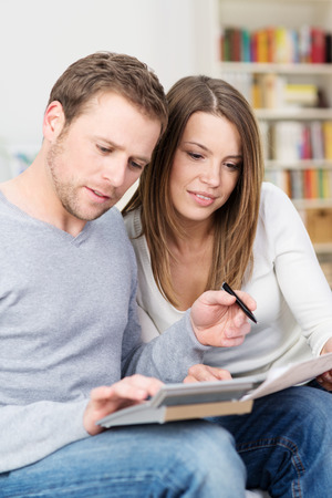 family budget: Young couple sitting checking their finances together as the husband checks figures on a document held by his wife on a calculator balanced on his knee