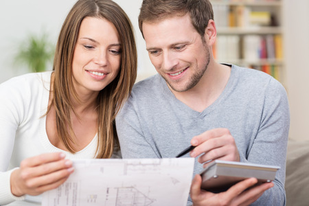 finance girl: Young couple planning a new purchase sitting together pointing to a document held by the wife as the husband does the necessary calculations on a calculator