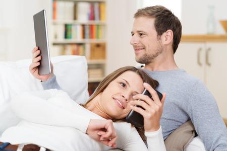 directorio telefonico: Pareja joven de relax juntos en el sofá mientras lee un libro electrónico en su tableta y ella consulta un mensaje de texto en su teléfono inteligente