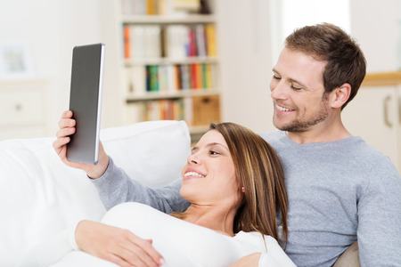 Young couple sharing a tablet computer as they relax together on a sofa with the wife reclining on her husbands chest Stock Photo - 27246820