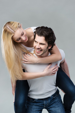 hair back: Playful couple riding piggy back together laughing as they young woman with long blond hair rides on her husbands back, on grey Stock Photo