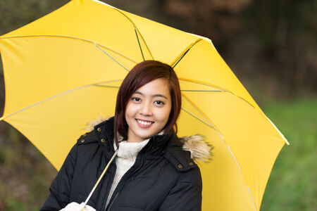 inclement: Attractive smiling young Asian woman sheltering under a yellow umbrella as she takes a walk outdoors on an inclement day
