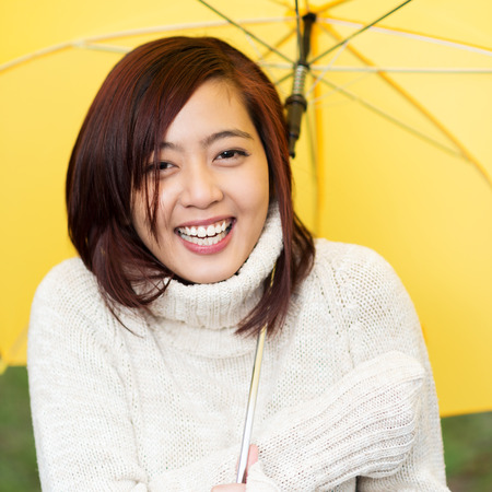 sheltering: Beautiful happy young Asian woman sheltering under a yellow umbrella in a warm polo neck sweater standing laughing at the camera