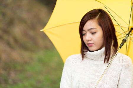 Sad wistful young Asian woman walking along outdoors under a yellow umbrella staring disconsolately at the ground photo
