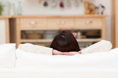 relajado: Vista desde detrás de una mujer joven que se relaja en su casa en un sofá con sólo la parte superior de su cabeza y sus brazos visible por encima de los cojines