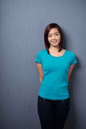 hands behind back: Attractive demure young Asian woman standing with her hands behind her back against a dark studio background with copyspace smiling at the camera Stock Photo