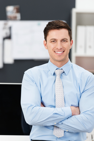 shirtsleeves: Confident sincere young businessman in his shirtsleeves standing leaning against his desk with folded arms smiling at the camera Stock Photo