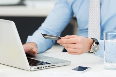 Zakenman die online bankieren, het maken van een betaling of de aankoop van goederen op het internet het invoeren van zijn credit card gegevens op een laptop, close-up bekijken van zijn handen Stockfoto