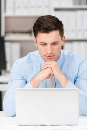 concentrates: Thoughtful young businessman sitting at his desk reading his laptop screen with his chin resting on his hands as he concentrates on the information, frontal view Stock Photo
