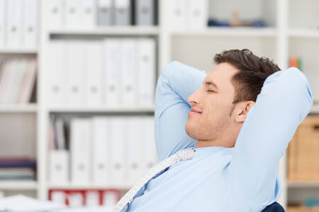 eye's closed: Contented businessman taking a break sitting back in his chair at the office with his hands clasped behind his head, eyes closed and a smile of pleasure