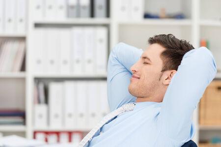 ojos cerrados: Hombre de negocios contento de tomar un descanso sentado atrás en su silla en la oficina con las manos entrelazadas detrás de la cabeza, los ojos cerrados y una sonrisa de placer