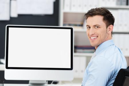 큰 빈 데스크톱 컴퓨터 모니터 선반 앞에 앉아 친절 젊은 사업가 웃는, 화면 완전히 보이는 카메라를 보면