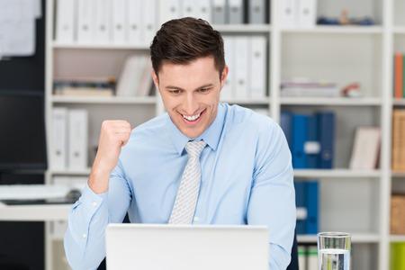 Jubelnden Geschäftsmann macht eine Faust und Jubel bei Informationen auf seinem Laptop-Computer-Bildschirm, wie er feiert einen Erfolg oder Leistung