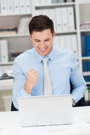 jubilation: Excited happy businessman punching the air in jubilation after learning of a successful business outcome Stock Photo