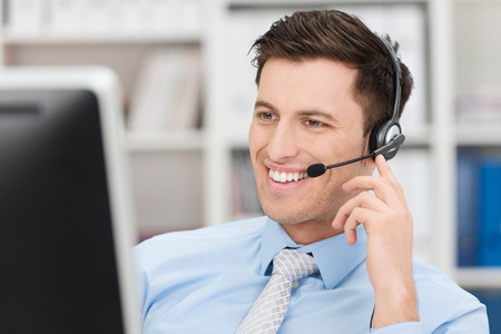 Smiling friendly handsome young male call centre operator or client services personnel beaming as he listens to a call and checks information on his computer monitor Stock Photo