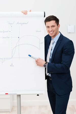 Handsome stylish young businessman giving a presentation on a flipchart smiling as he looks up at the camera photo