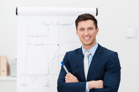 instructors: Confident young team leader or manager standing in front of a flip chart smiling at the camera with folded arms