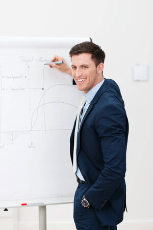 Confident businessman giving a presentation as he stands in front of a flip chart drawing a graph and turning to smile at the camera photo