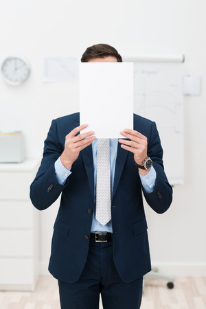 businessman pondering documents: Elegant Businessman in a stylish suit hiding his face behind a blank white sheet of paper with copyspace for your text