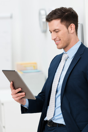 Stylish young businessman standing reading a handheld tablet computer smiling at the information on the screen photo