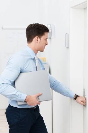 Businessman opening a door as he leaves the office with a binder under his arm photo