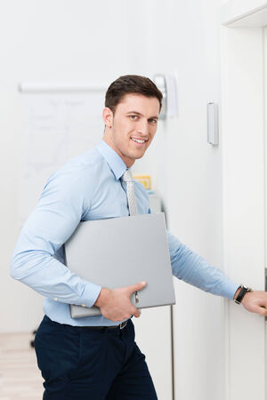 Busy young businessman leaving the office with a folder under his arm reaching out to open the door photo