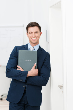 candidates: Smiling confident young job applicant holding his curriculum vitae in his folded hands leaning against a wall in a relaxed position smiling at the camera Stock Photo