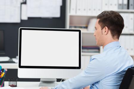 computer screen: Uomo d'affari che lavora alla sua scrivania con lo schermo vuoto del suo computer desktop visibile per lo spettatore