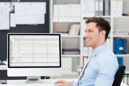 左側の画面オフ誰かに笑みを浮かべて彼のデスクトップのモニターでスプレッドシートに取り組んで彼の机で笑顔の自信を持って実業家