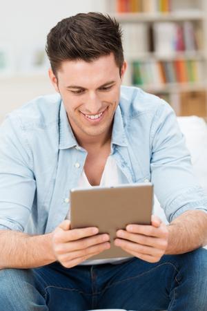 beau jeune homme: Beau jeune homme lisant un livre �lectronique ou des informations sur son ordinateur tablette souriant � la teneur comme il se d�tend � la maison