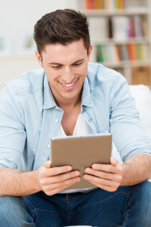 handsome young man: Handsome young man reading an e-book or information on his tablet computer smiling at the content as he relaxes at home