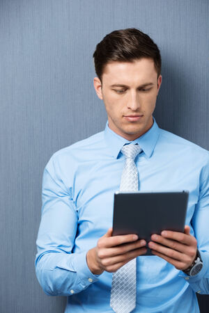 Businessman standing against a green background reading information on his handheld tablet computer with a serious expression photo