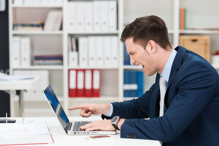 Businessman screaming in horror and pointing at his laptop as he reads something upsetting on the screen, side view in the office photo