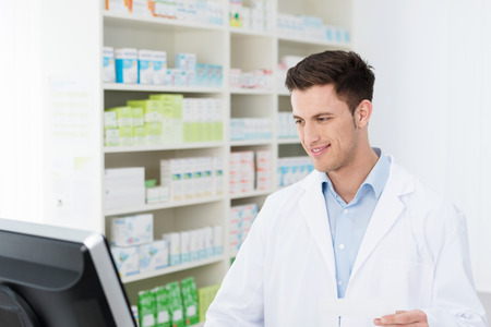 dispense: Smiling young male pharmacist standing checking stock on his computer in the pharmacy as he prepares to dispense medication