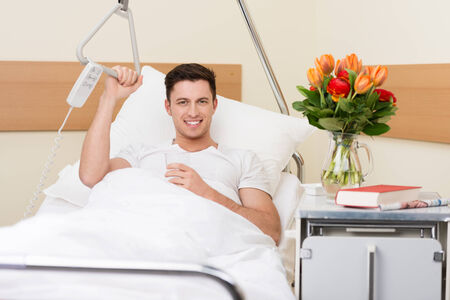 recuperating: Handsome young man recuperating in a hospital sitting up in bed with a cheerful smile and a big bouquet of flowers on the night stand
