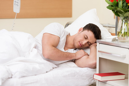 restful: Young man having a restful sleep in a hospital bed with his book on the night stand alongside him as he recuperates from an illness or injury Stock Photo