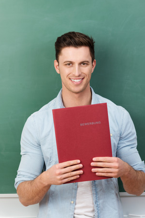 Smiling handsome young male student or job applicant holding a file containing his curriculum vitae detailing his experience and qualifications photo