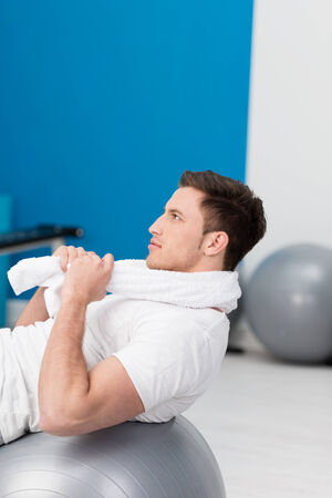 pilates man: Young man working out using a gym ball doing pilates exercises using his back muscles to balance as he grips a towel around his neck with his hands Stock Photo
