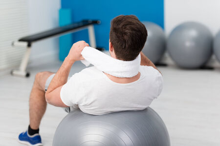 pilates man: View from behind of a man holding a white towel around his neck doing pilates exercises at the gym