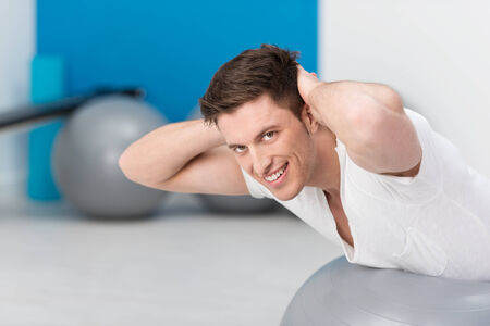 pilates man: Healthy fit young man doing pilates exercises balancing over the gym ball to strengthen his muscles and smiling at the camera Stock Photo