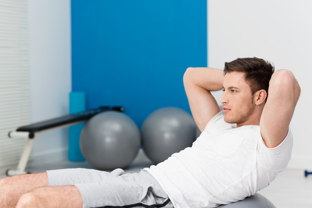 toning: Young man working out at the gym doing pilates exercises balancing over the ball with his hands clasped behind his head toning his muscles and staring ahead with a serious expression, side view