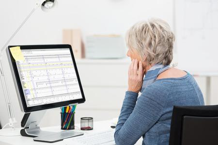大型のデスクトップ モニター上のスプレッドシートを勉強してオフィスで彼女の机で働く高齢者、女性実業家の側面図 写真素材