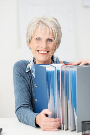 upright row: Happy contented senior businesswoman holding onto a row of files standing upright on her desk smiling at the camera